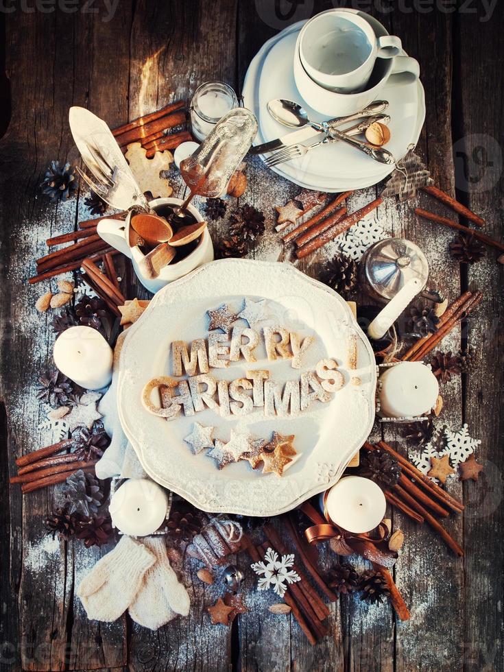 merry christmas decor op houten tafel. gebakken letters. bovenaanzicht foto