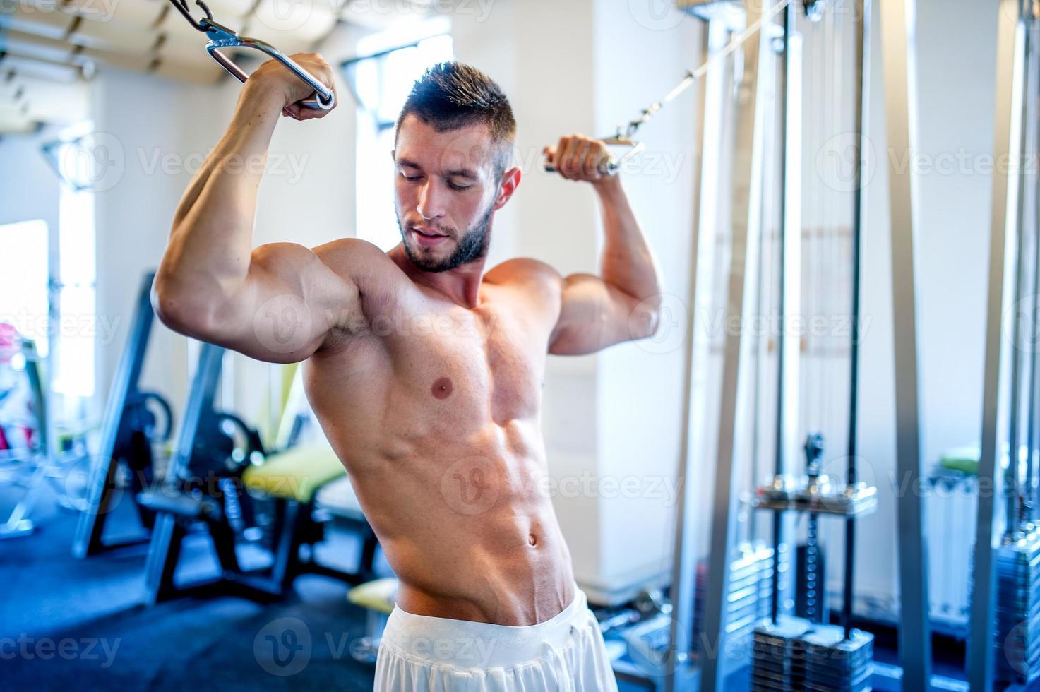 trainer, bodybuilder de biceps in de sportschool uit te werken foto