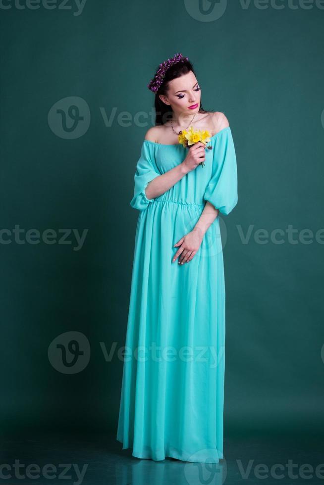 meisje met krans van bloemen in blauwe mode jurk foto