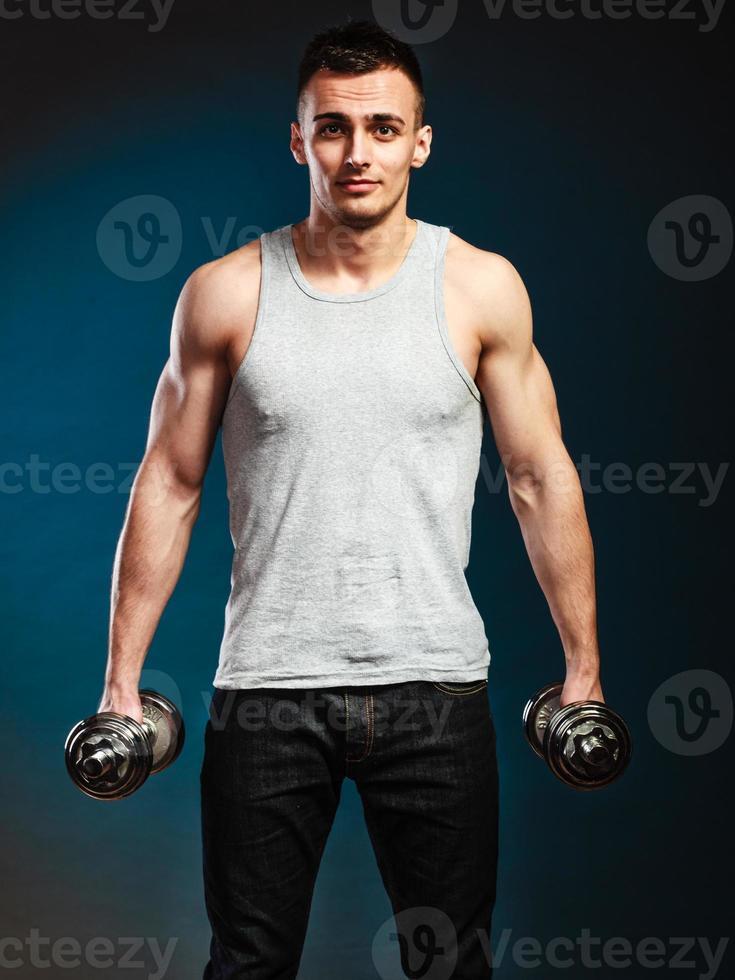 atletische man aan het werk met zware halters foto