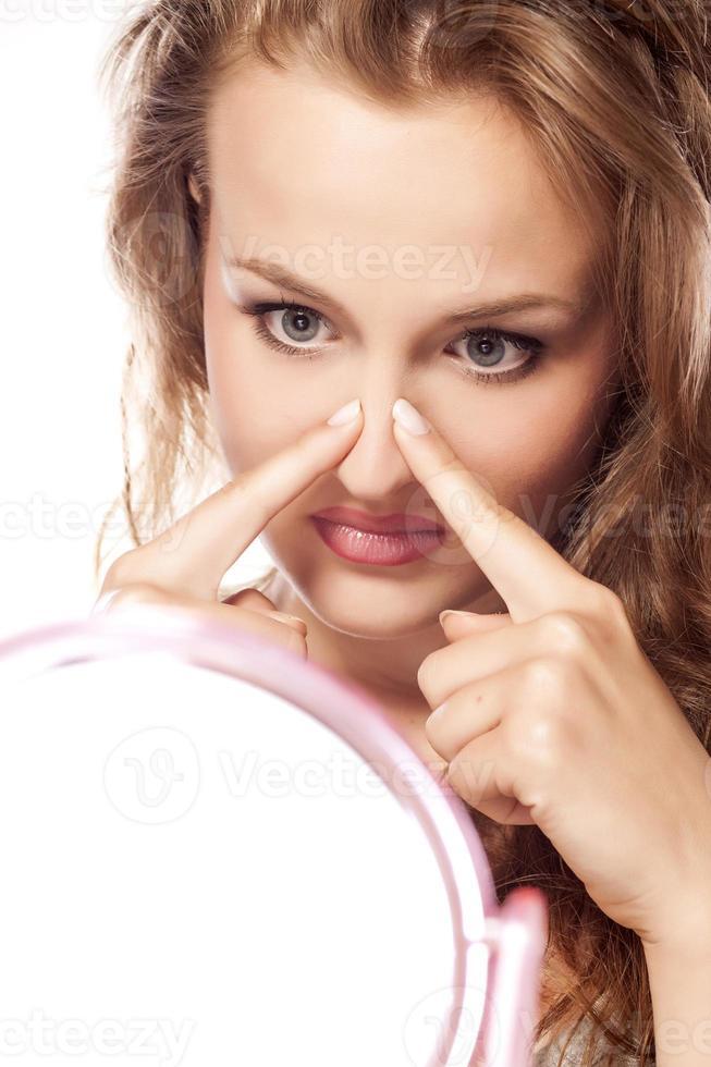 teleurgestelde jonge blonde aanraken van haar neus in de spiegel foto