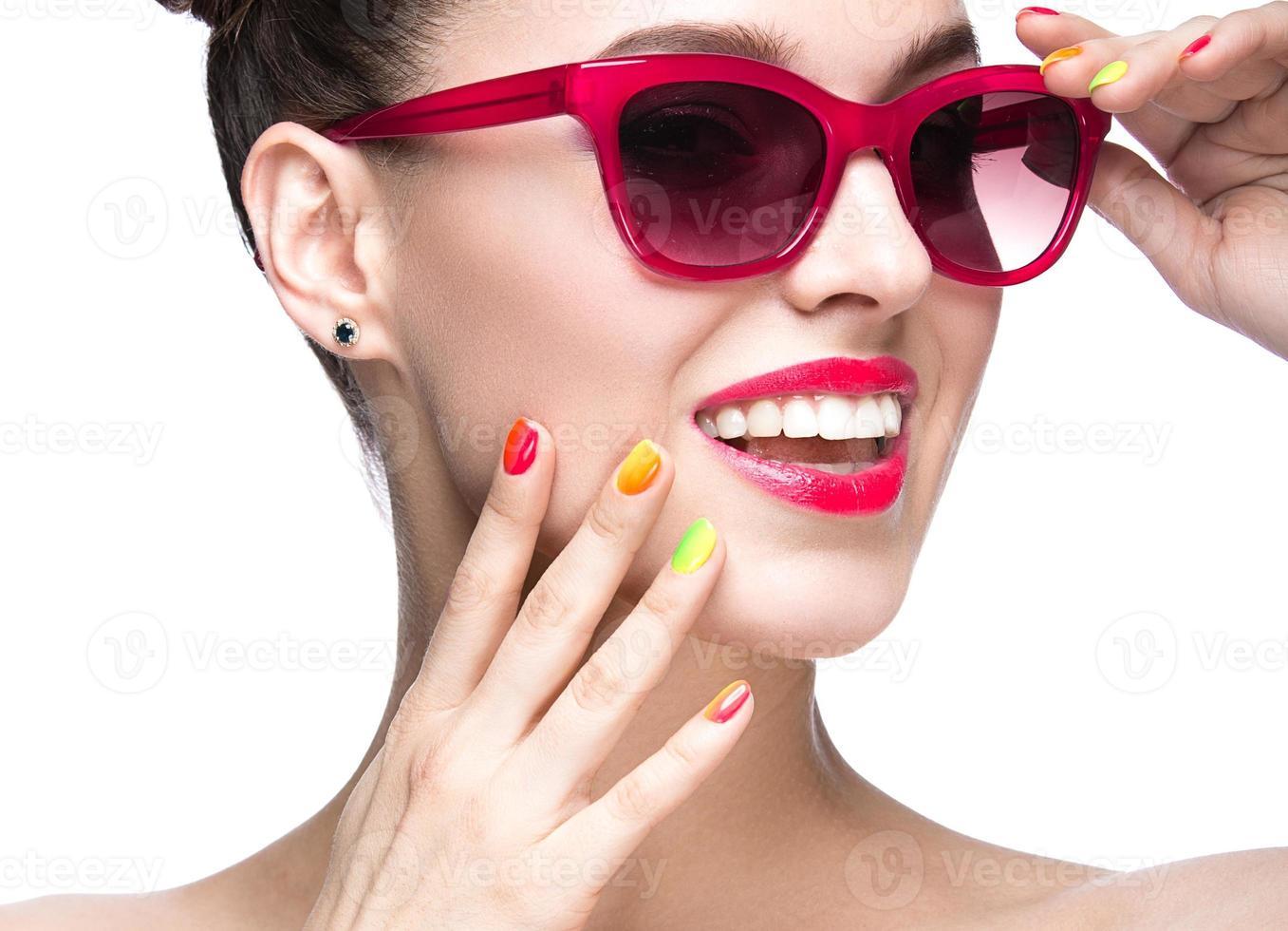 meisje in rode zonnebril met lichte make-up en kleurrijke nagels. foto