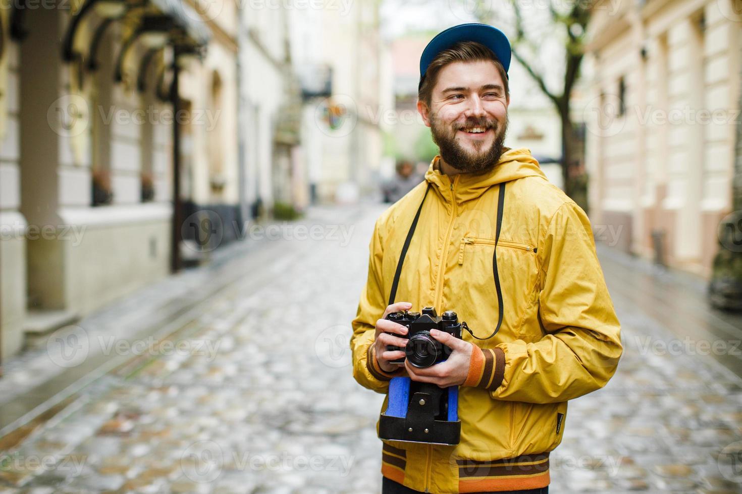 hipster met camera op zoek naar de zijkant en lachen foto