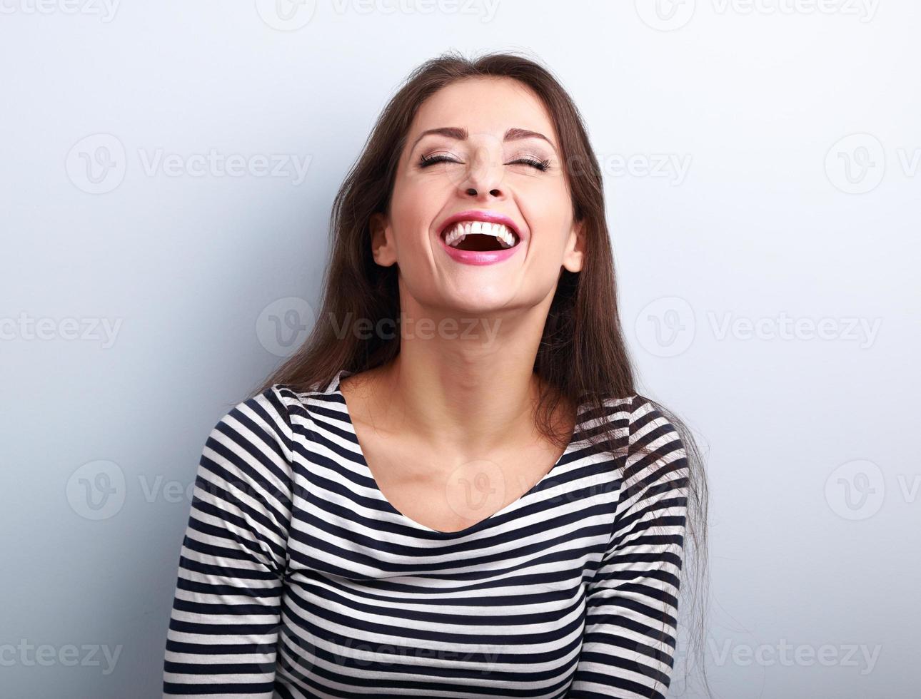 gelukkig natuurlijke lachen jonge casual vrouw met wijd open mond foto