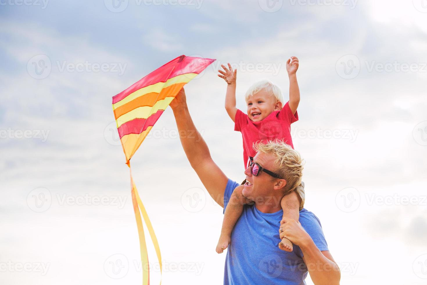 vader en zoon spelen met kite foto