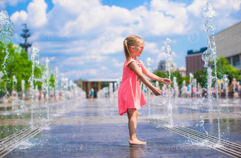 schattig klein meisje spelen in straat fontein foto
