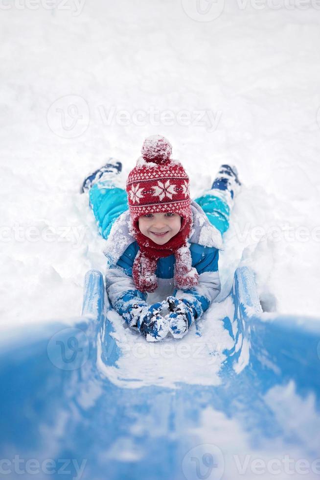 schattige kleine jongen, naar beneden een besneeuwde glijbaan foto