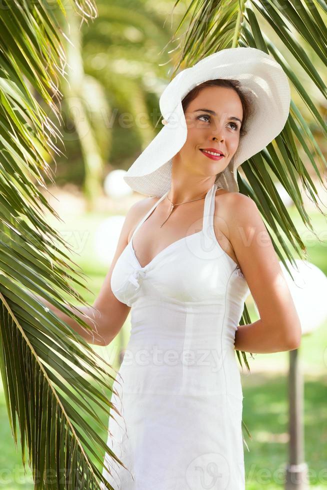 vrouw ontspannen onder palmboom foto