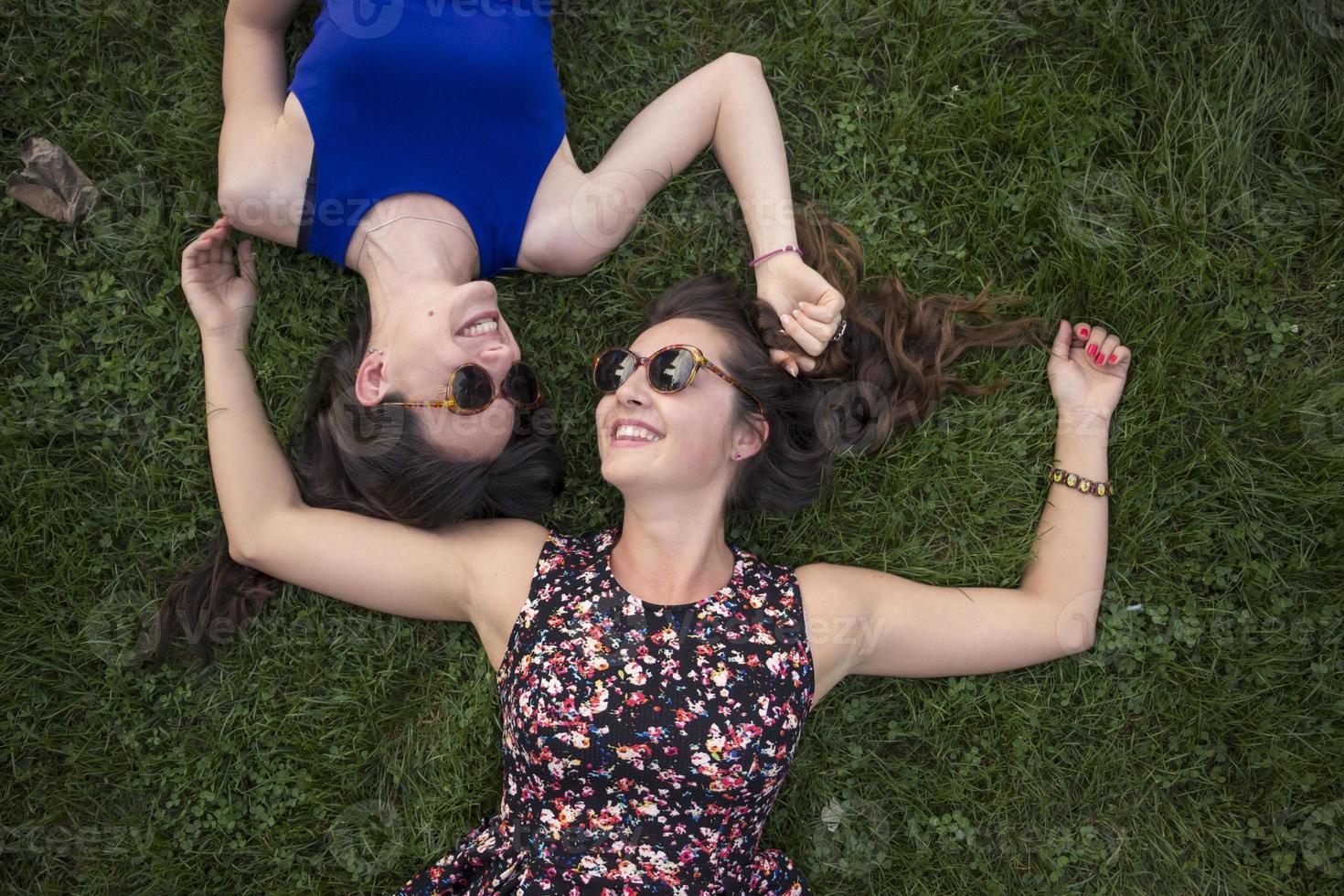 twee intieme schattige meisjes, ontspannen in het gras. foto