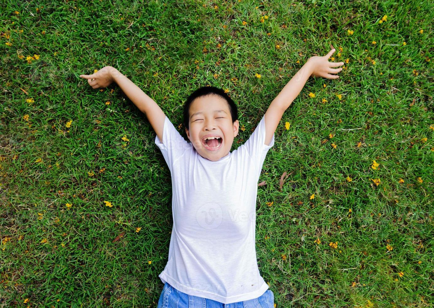 jongen lag op het gras voel me ontspannen foto