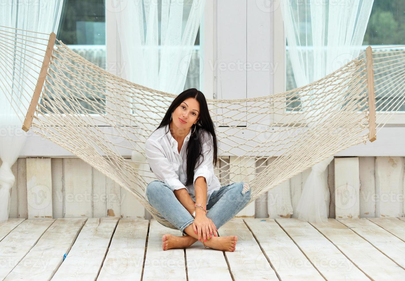 mooie lachende jonge vrouw ontspannen in een hangmat thuis foto