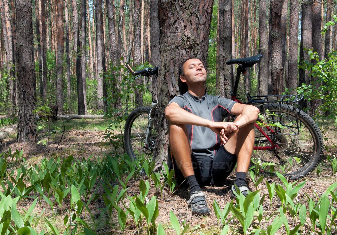ontspannende fietser in naaldbos de lente onder pijnboom foto