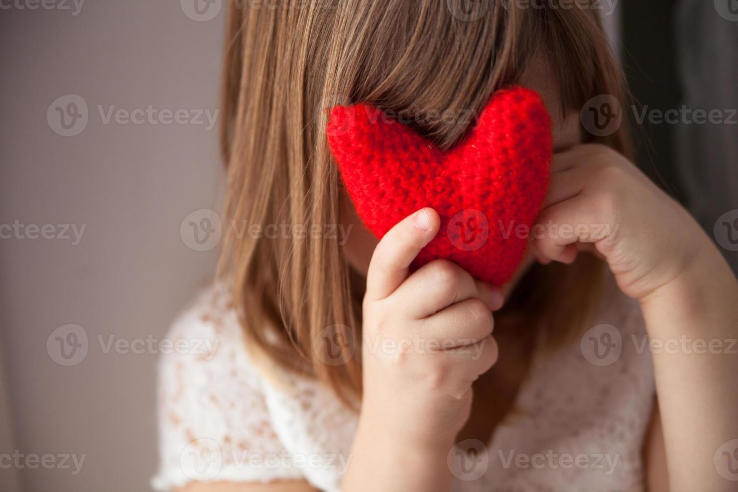meisje verstopt achter een gebreid rood hart, Valentijnsdag, foto