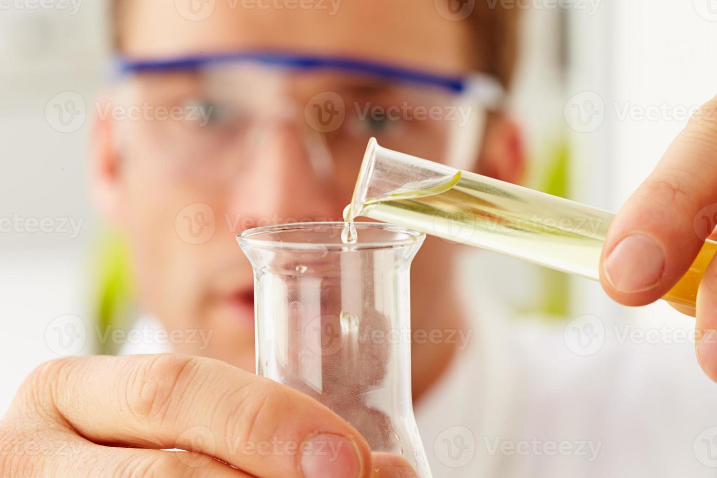 wetenschapper gieten vloeistof uit reageerbuis in kolf foto