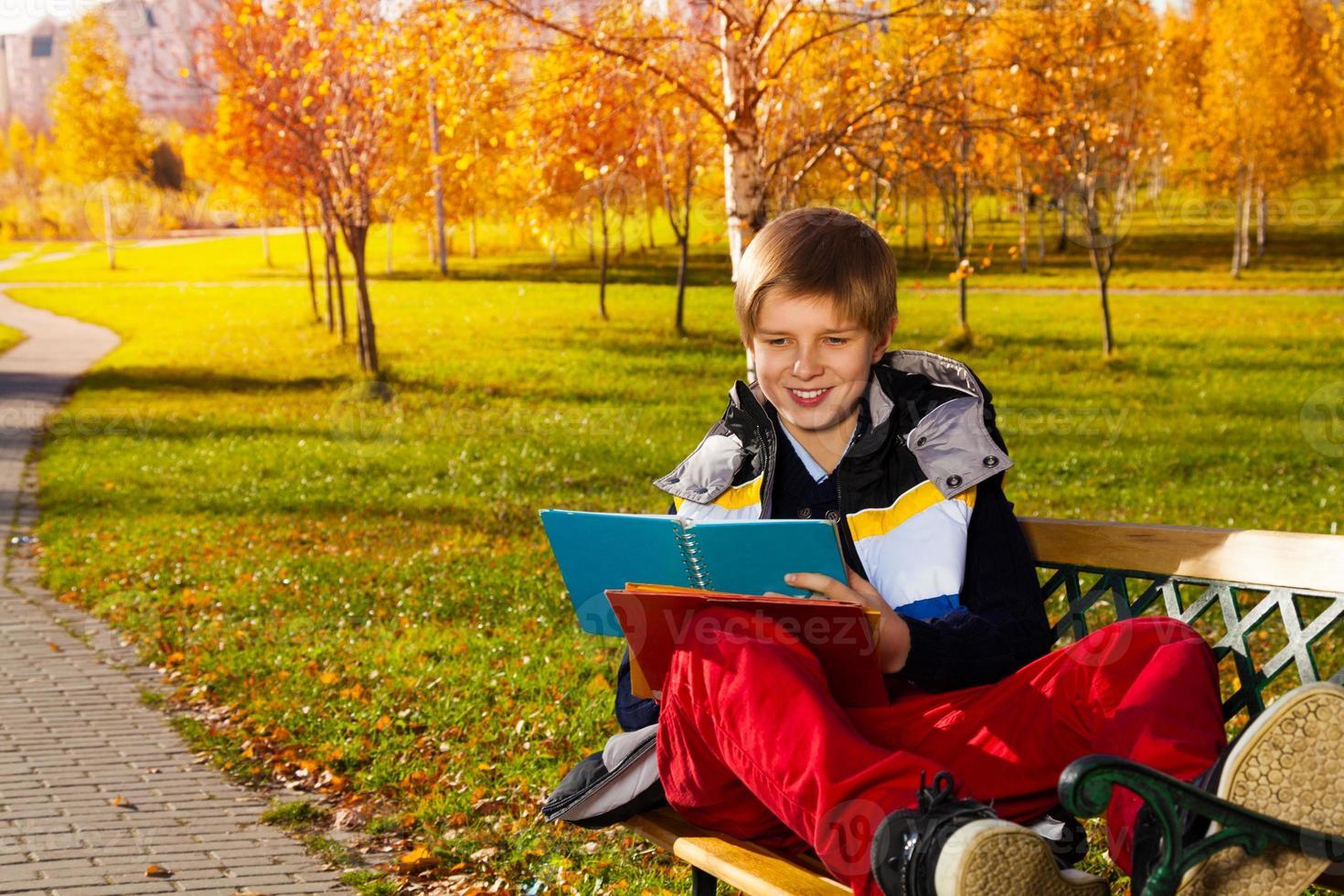 lachende jongen met leerboek foto