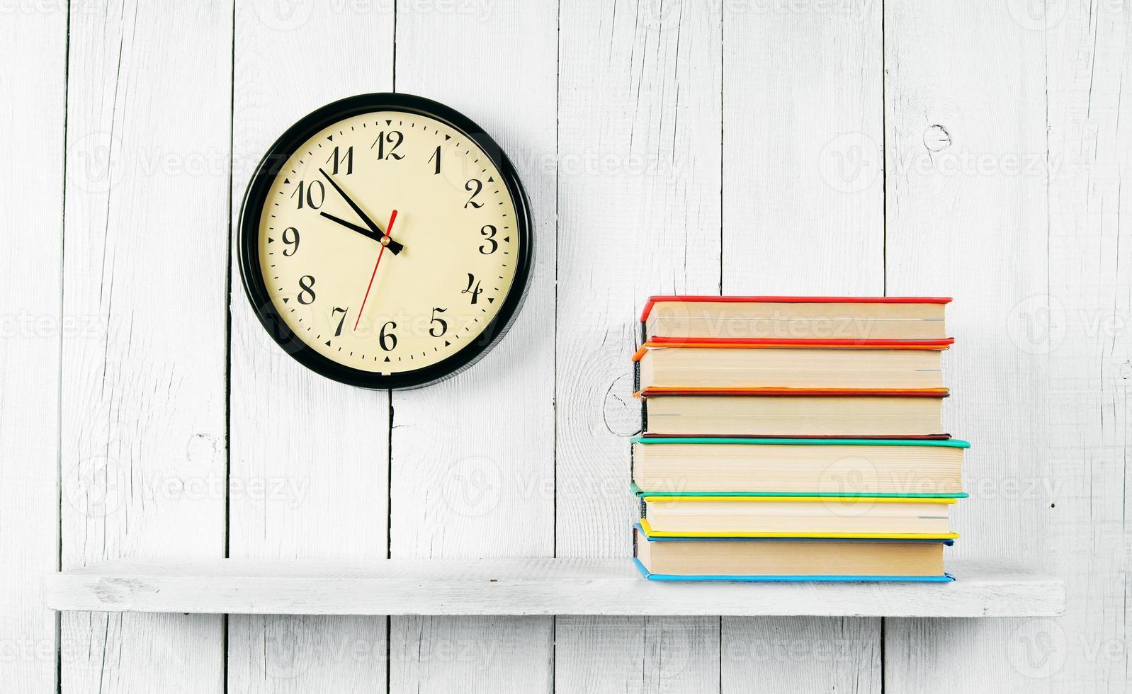horloges en boeken op een houten plank. foto