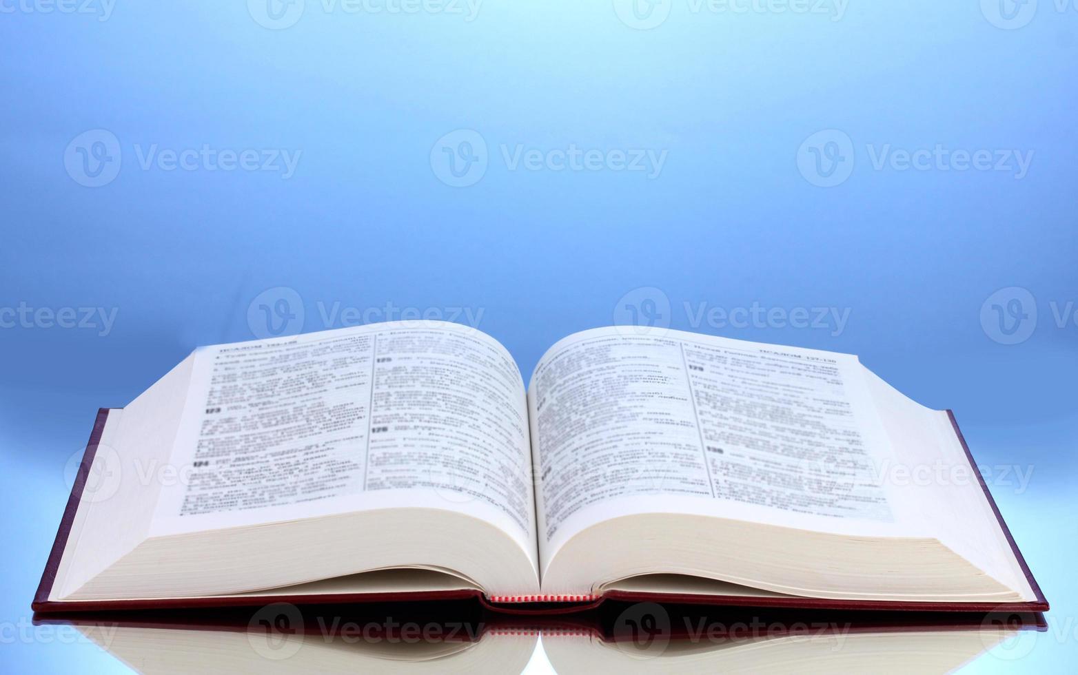 open boek over reflecterend oppervlak van tabel op blauwe achtergrond foto