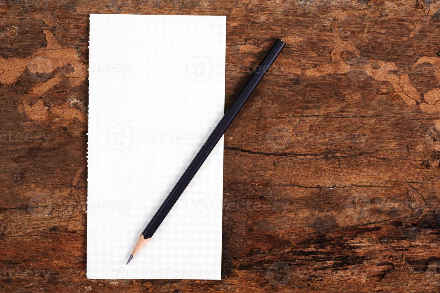 oude pagina opgelicht uit het notitieblok op houtstructuur foto