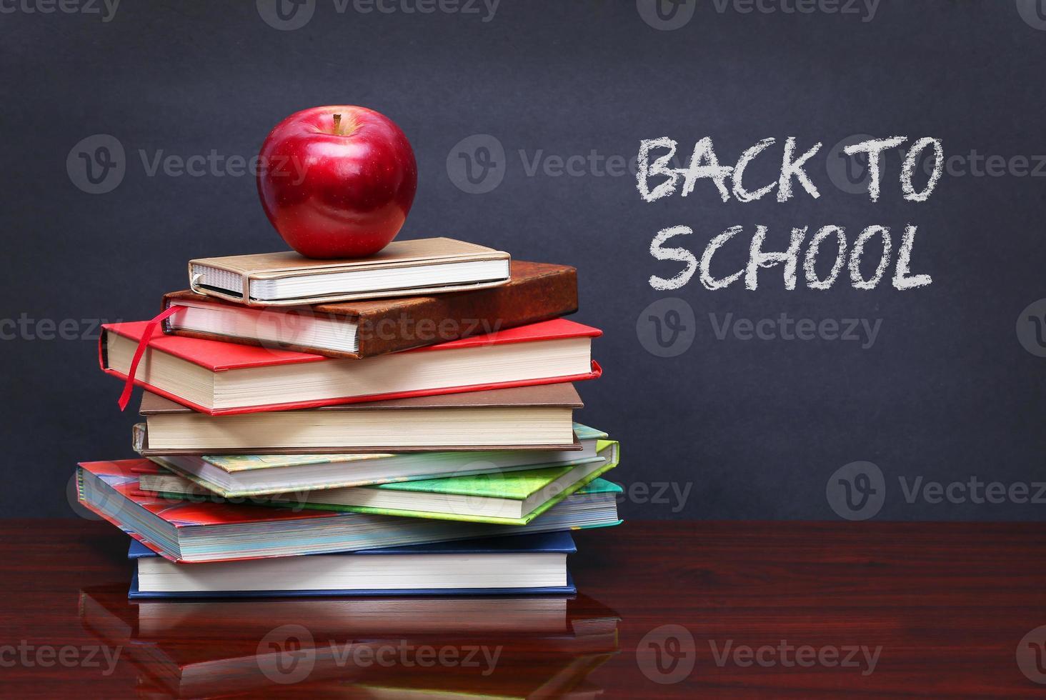 stapel boeken en rode appel op het bureau foto
