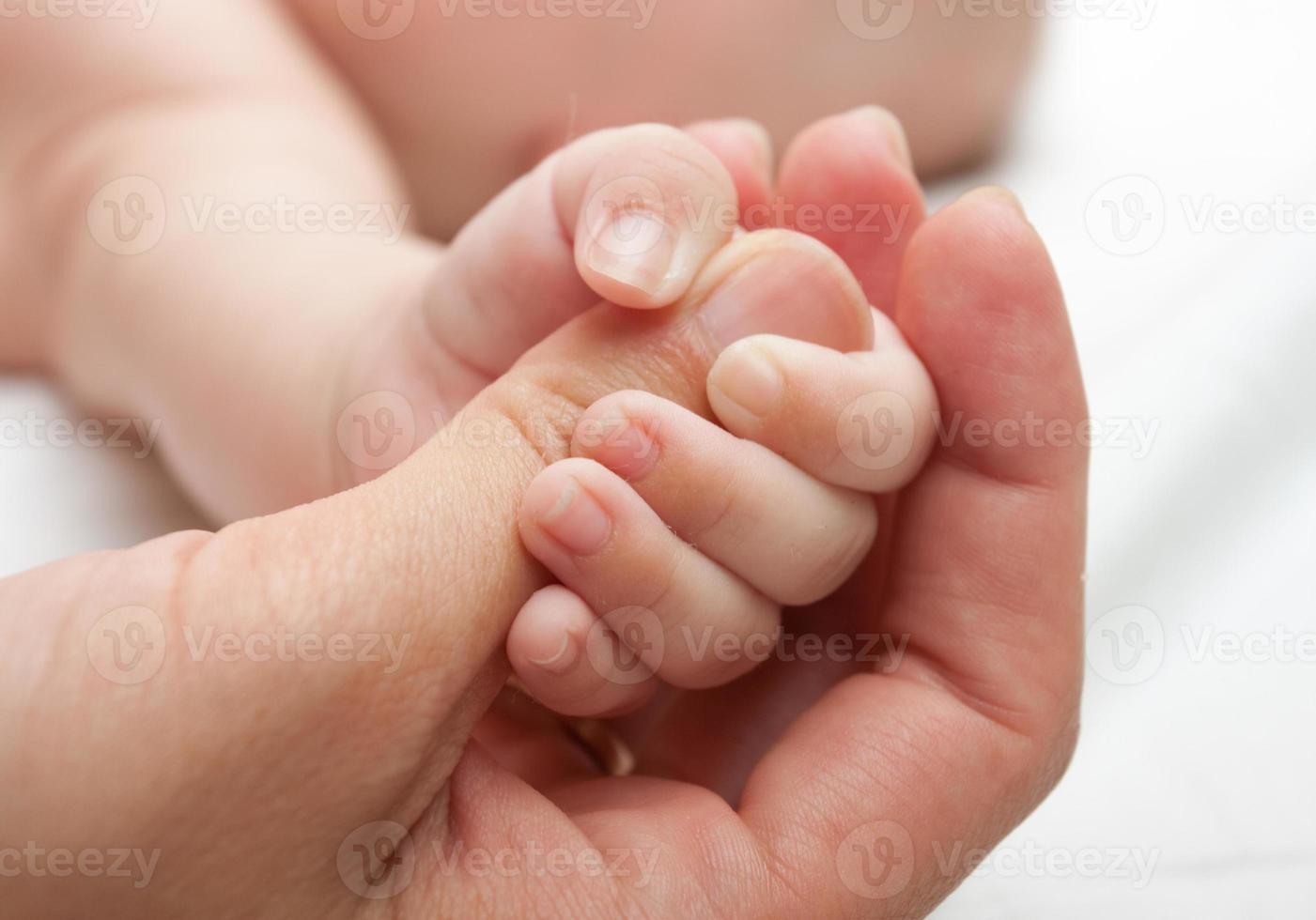 close-up van een baby die de duim van een volwassene houdt foto
