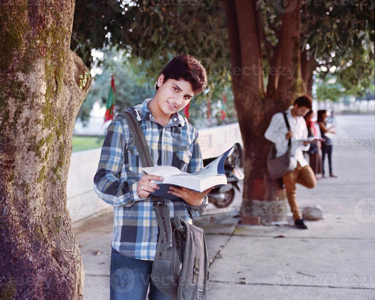 mannelijke student studeert in de buurt van de parkeerplaats. foto
