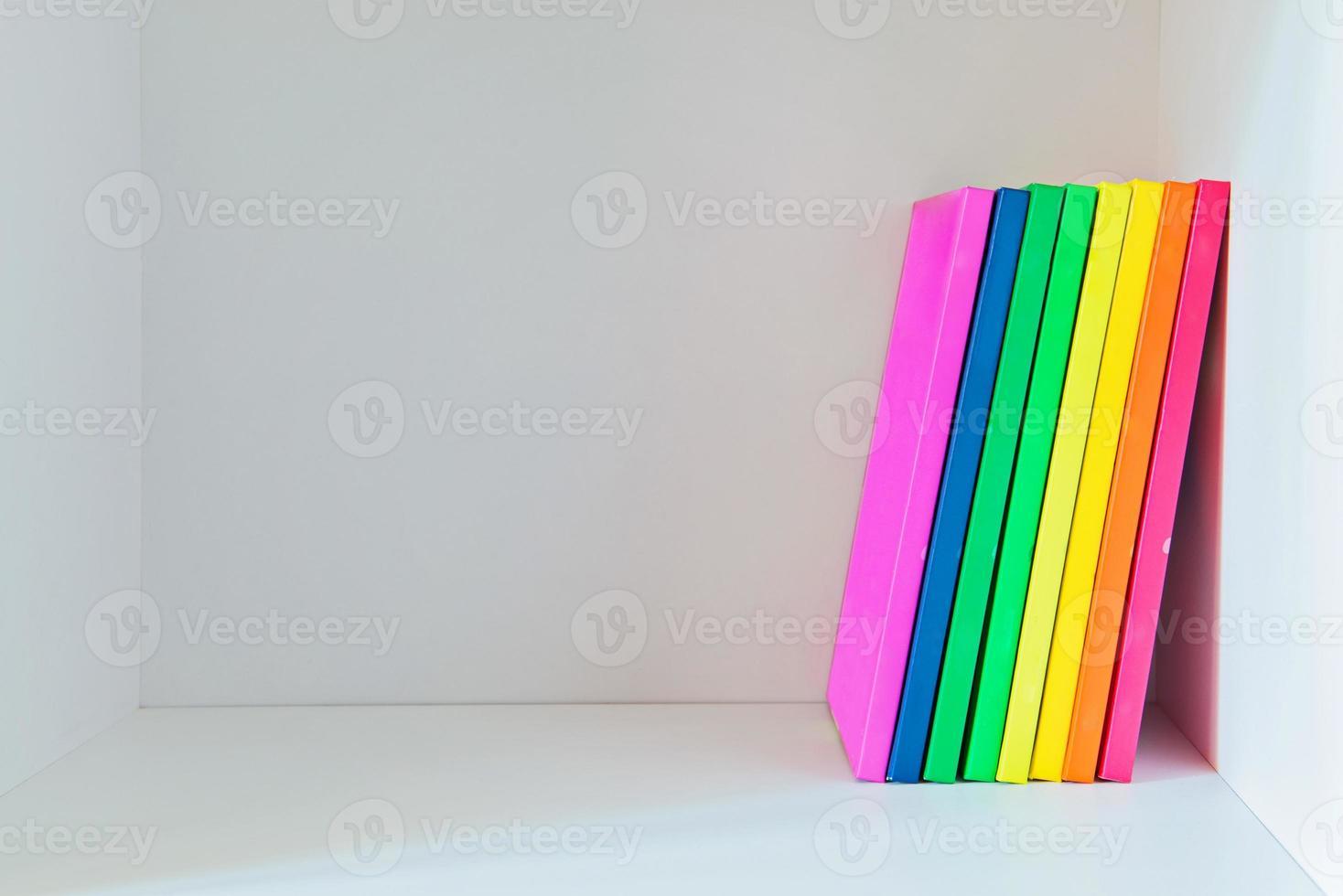 veelkleurige boeken op de lichtgekleurde boekenplank foto