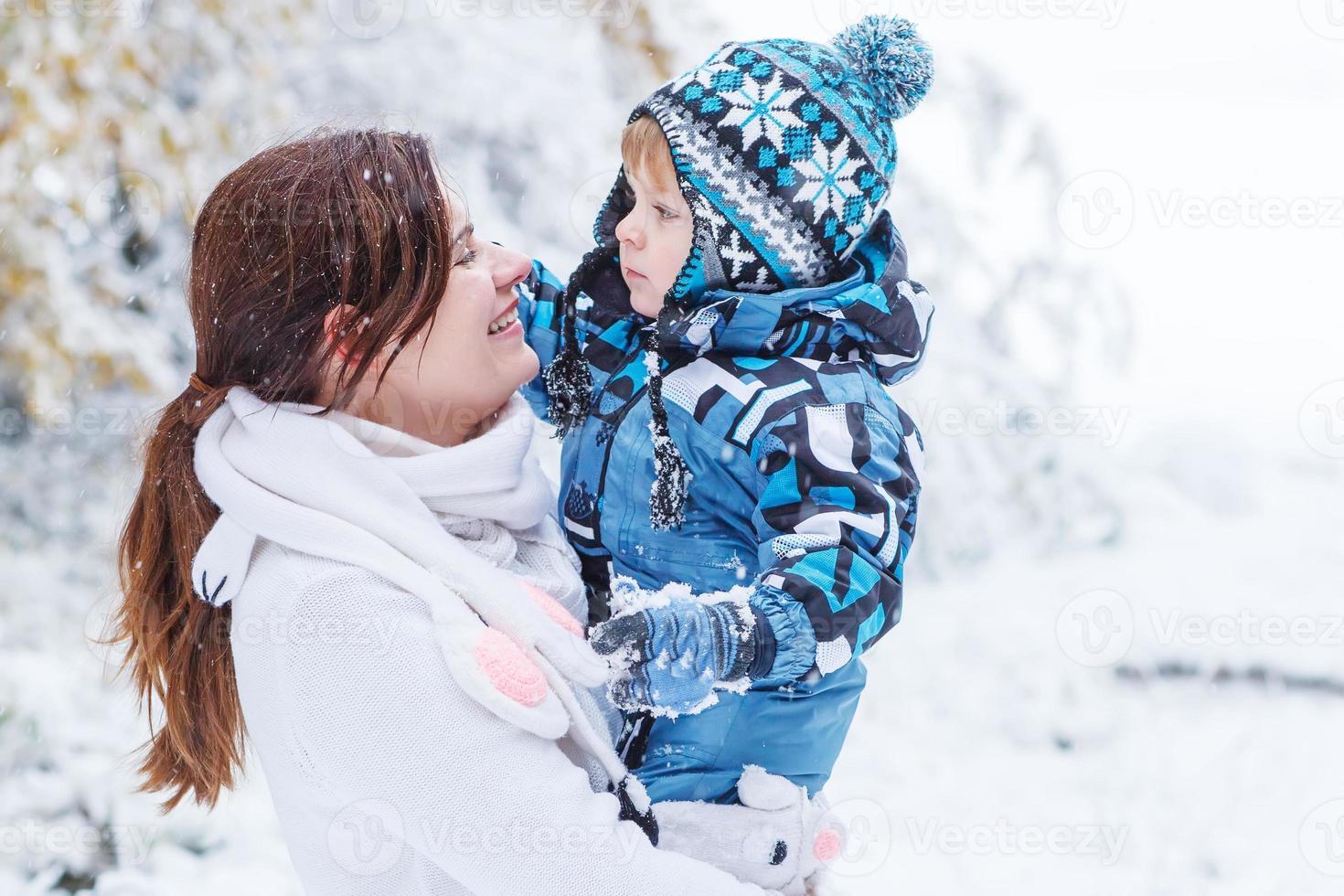 kleine preschool jongen en zijn moeder spelen met eerste sneeuw foto