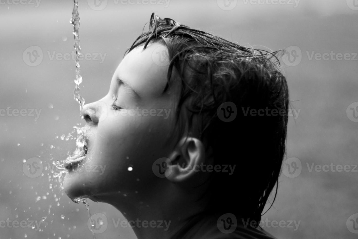 druppels water spatten op het gezicht van de jongen foto
