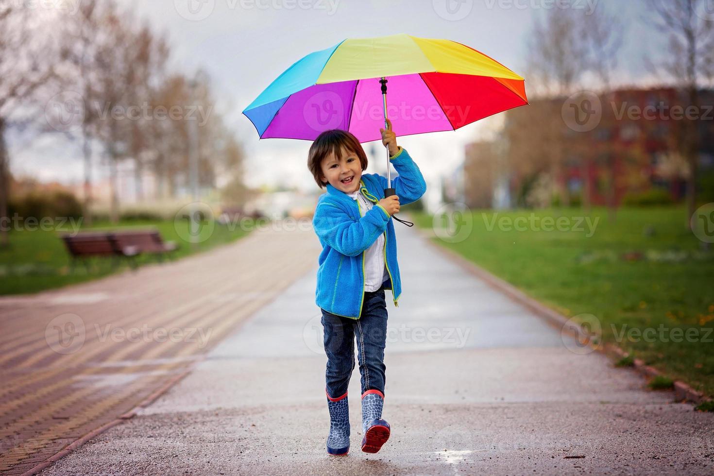 schattige kleine jongen, wandelen in een park op regenachtige dag foto