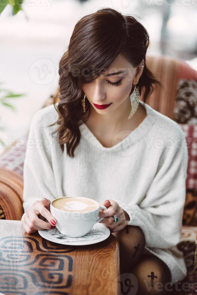 jong meisje koffie drinken in een trendy café foto