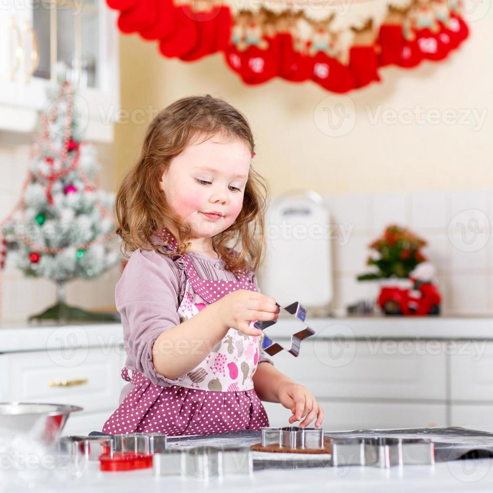 klein meisje peperkoek koekjes bakken in de binnenlandse keuken foto