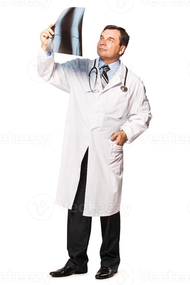 volwassen mannelijke radioloog die de röntgenfoto van de patiënt bestudeert foto
