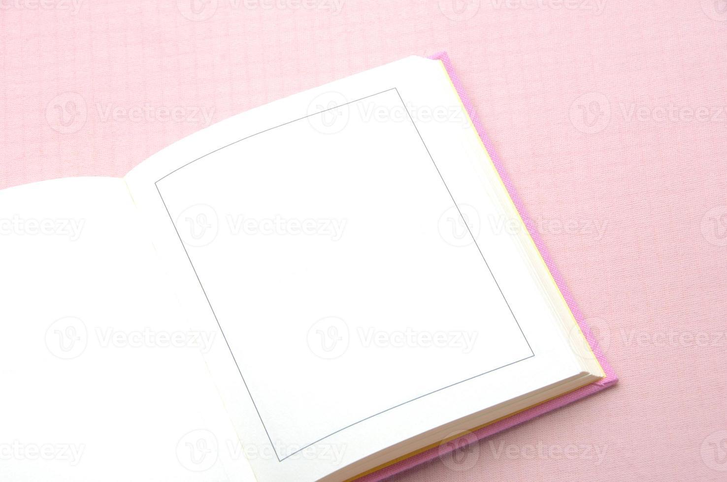 geopend boek op roze achtergrond foto