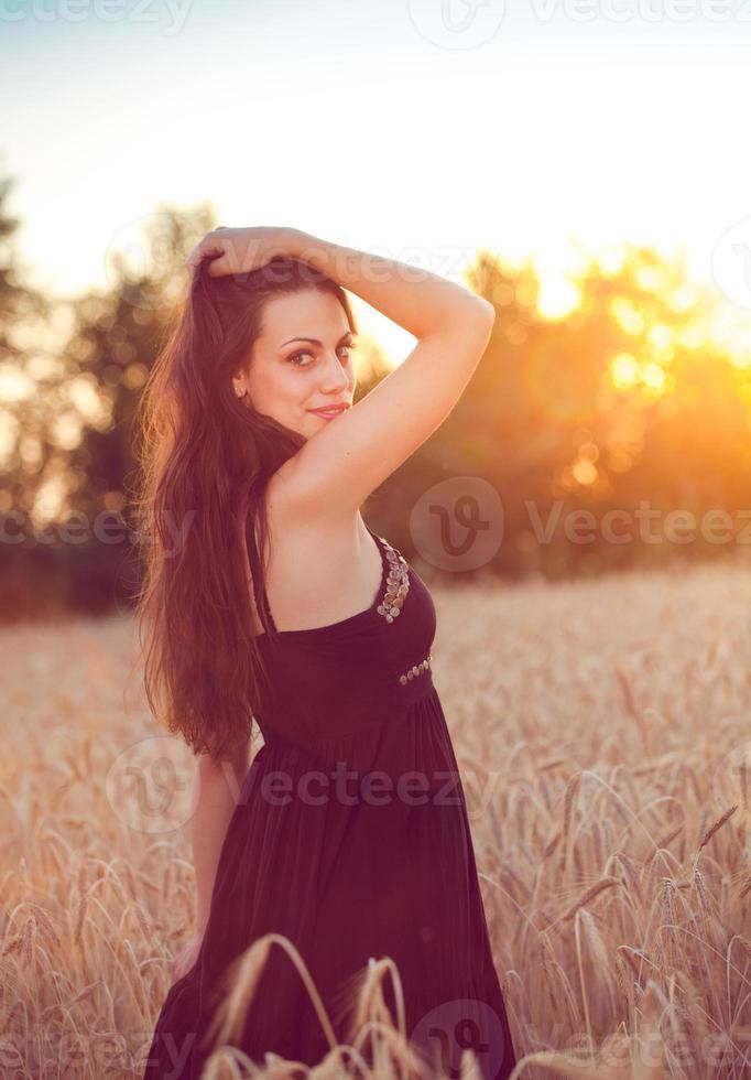 mooi meisje in een tarweveld bij zonsondergang foto