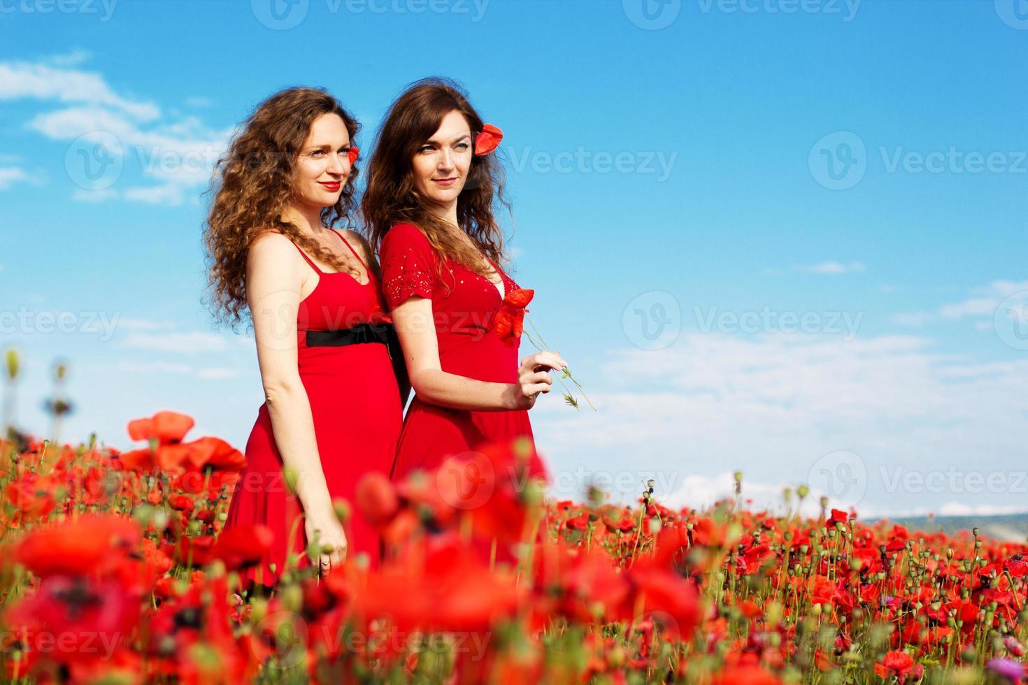 twee jonge vrouwen spelen in papavers veld foto