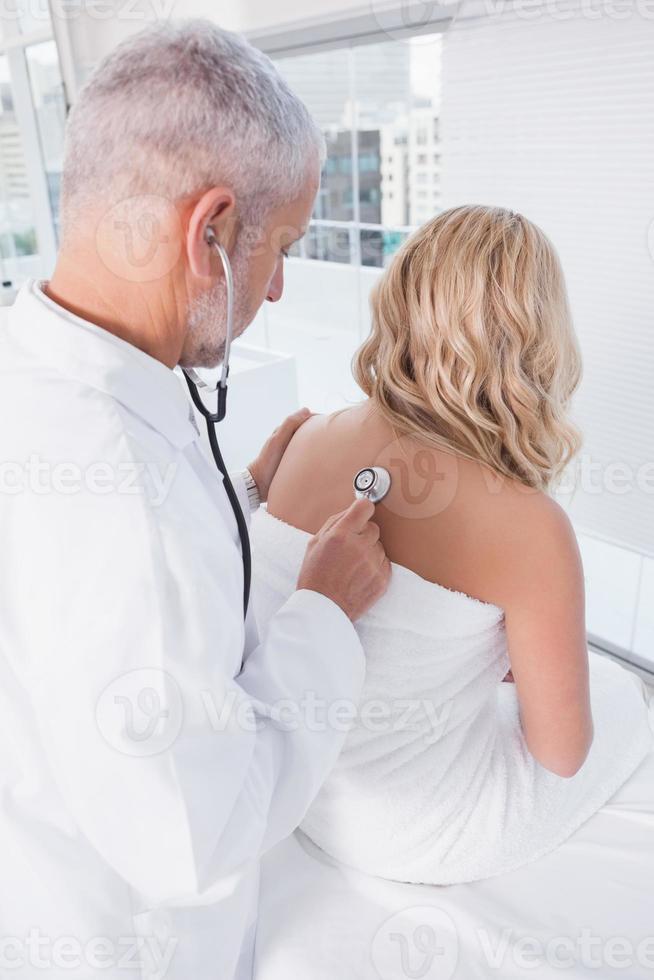 arts die de ademhaling bij zijn patiënt luistert foto