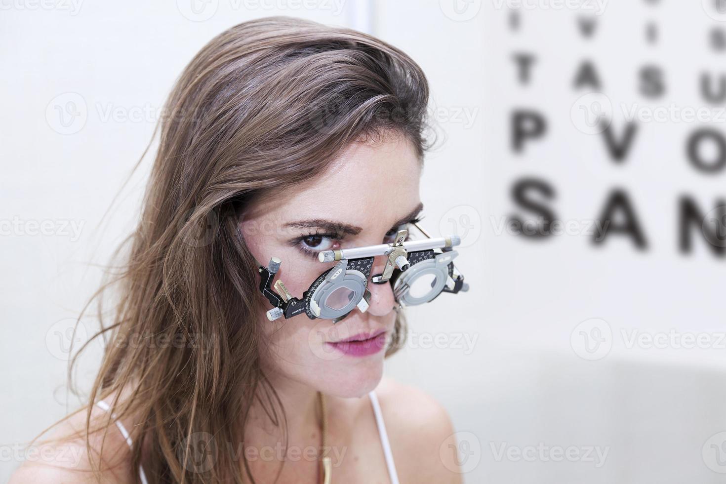 mooie vrouw test nieuwe hulplenzen met phoropter foto