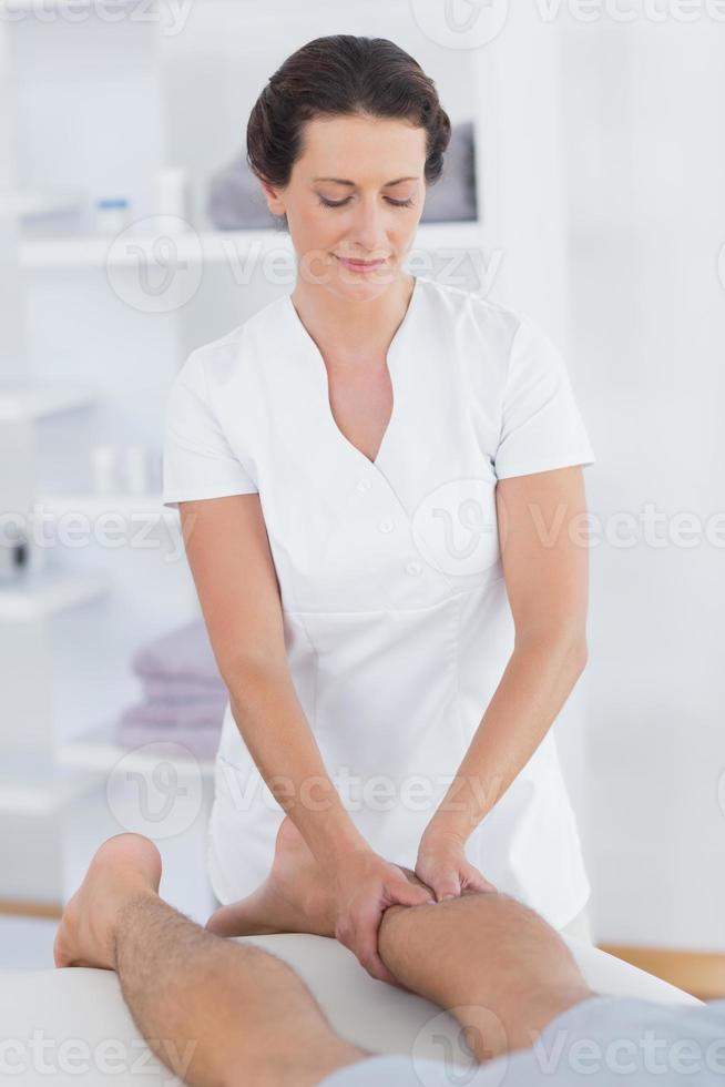 fysiotherapeut die kalfsmassage doet aan haar patiënt foto