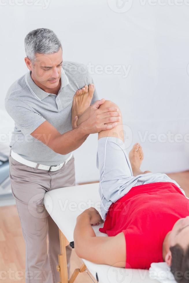 man met beenmassage foto