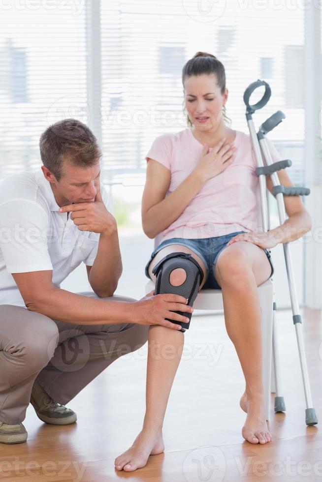 arts die zijn geduldige knie onderzoekt foto