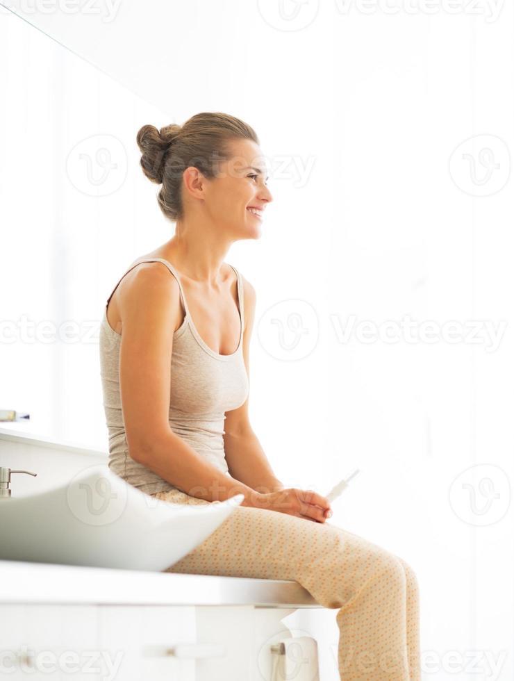 portret van gelukkige jonge vrouw met zwangerschapstest in de badkamer foto