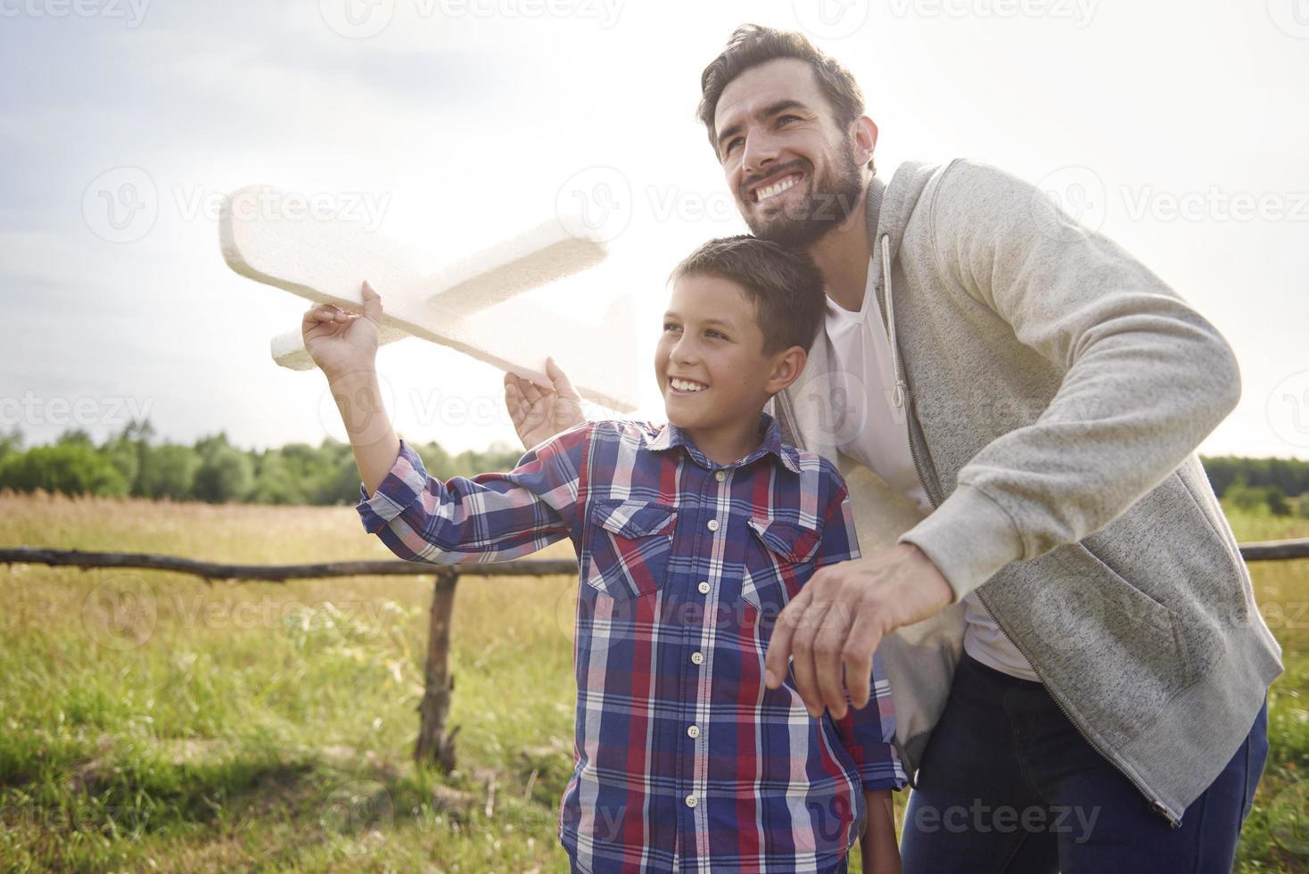 vader en zoon testen een papieren vliegtuig foto
