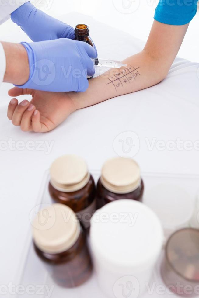 arts doet huidpriktest bij zijn patiënt foto