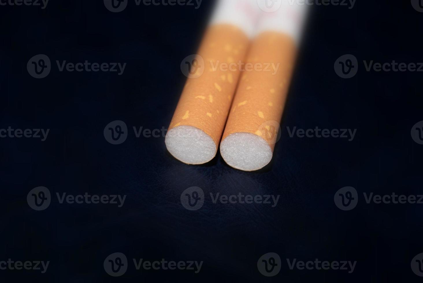 twee sigaretten geïsoleerd op zwart foto