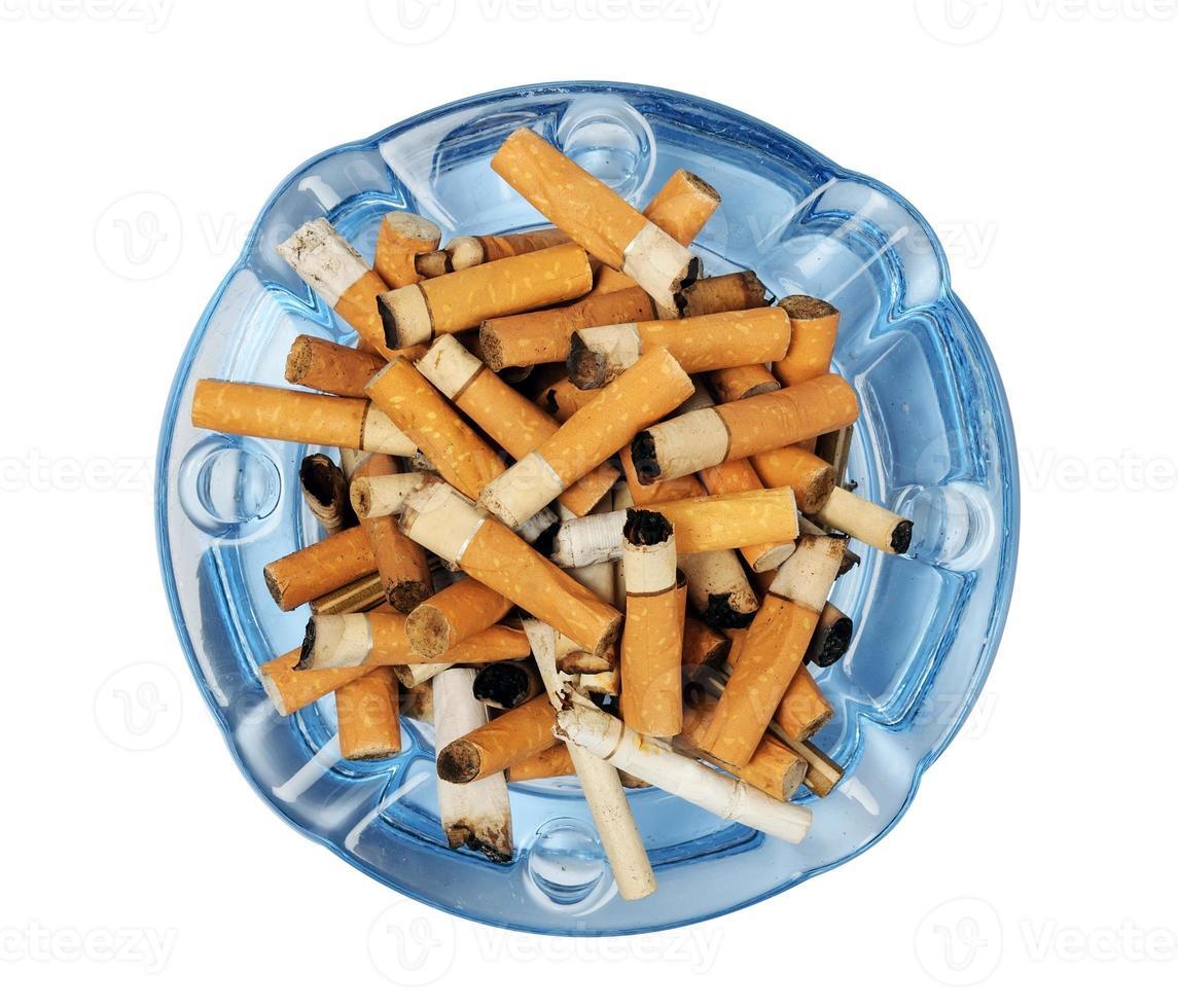 sigaretuiteinden in de asbak die op wit wordt geïsoleerd foto