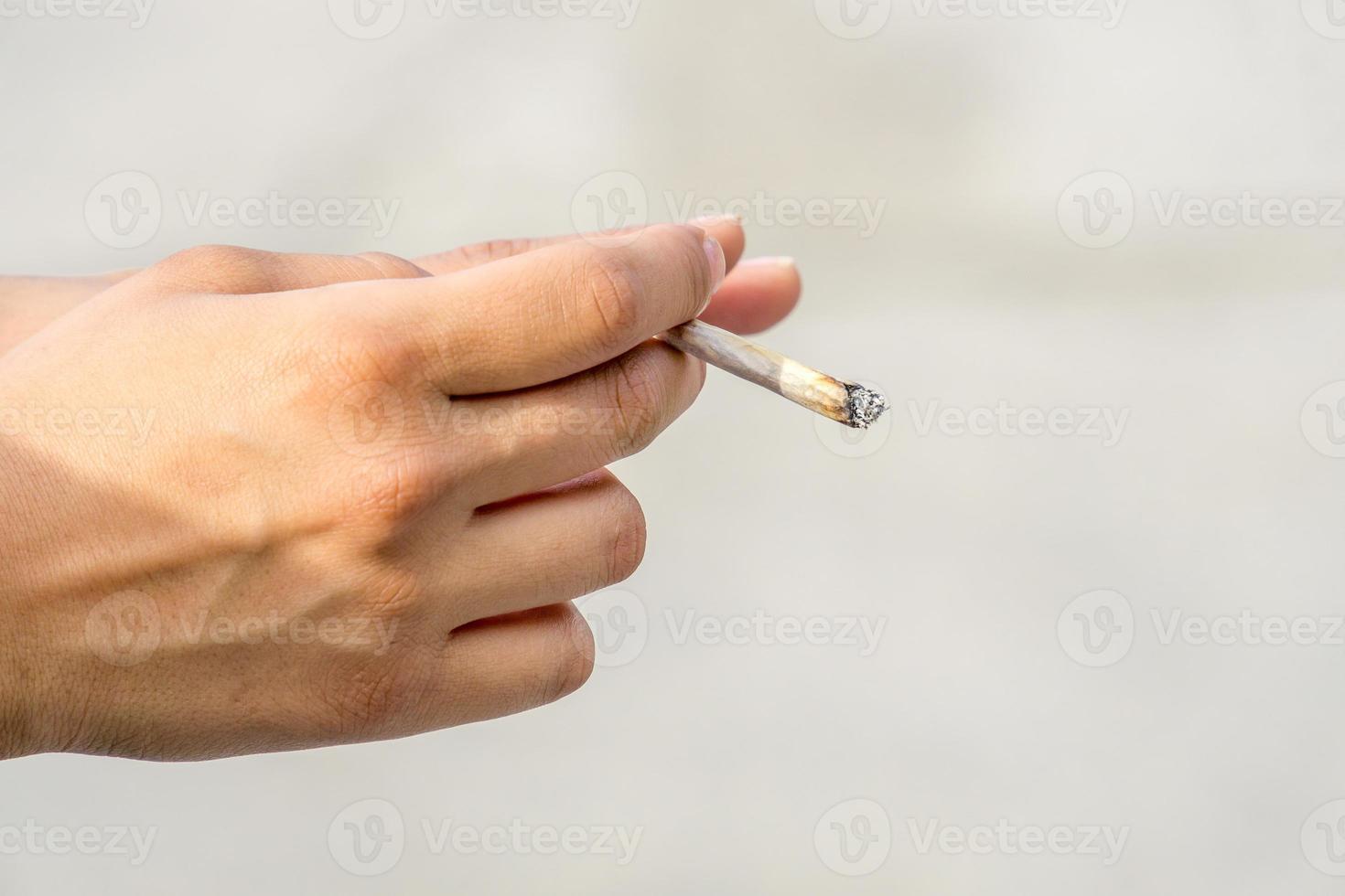 hand met gerolde sigaret of joint foto
