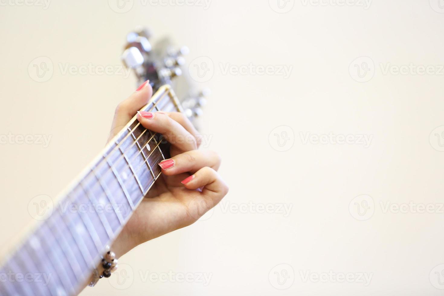 vrouw muzikant met een gitaar, spelen een akkoord foto