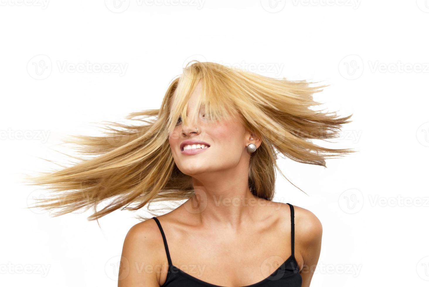 mooie blonde vrouw haar haren schudden foto