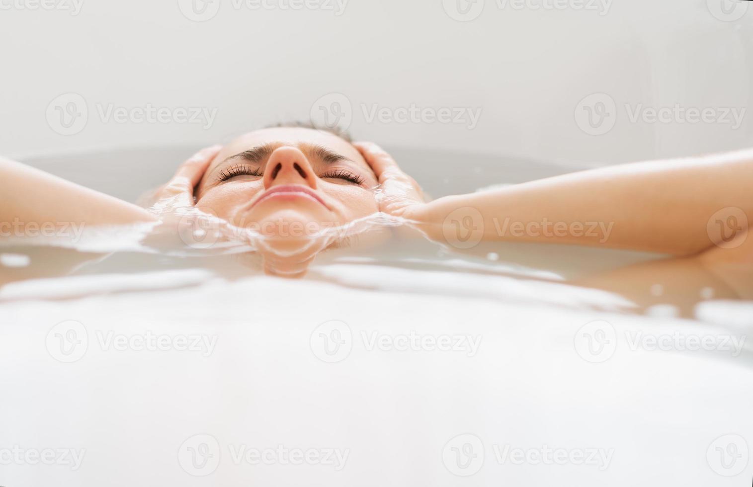 beklemtoonde jonge vrouw die in badkuip legt foto