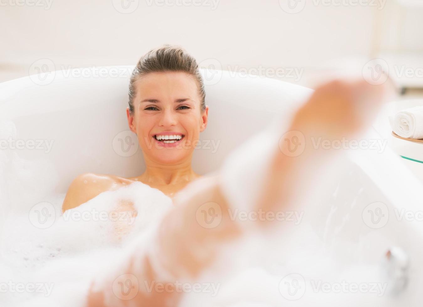 glimlachende jonge vrouw die prettijd in badkuip heeft foto